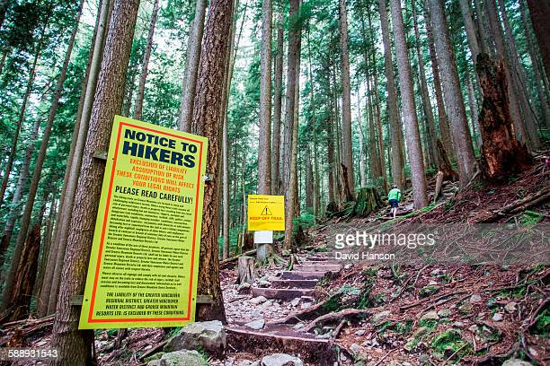 vancouver, british columbia, canada. a man walks up a steep trail past a giant yellow sign full of legal disclaimers and keep off trail warnings. - grouse mountain stock photos and pictures