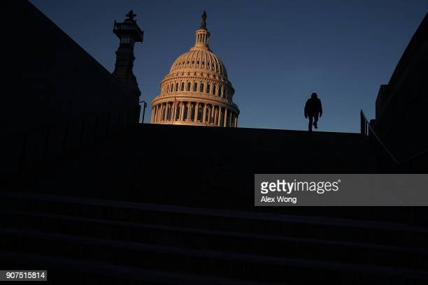 A man walks up the steps in front of the US Capitol in the morning hours January 20 2018 in Washington DC The US government is being shut down after...