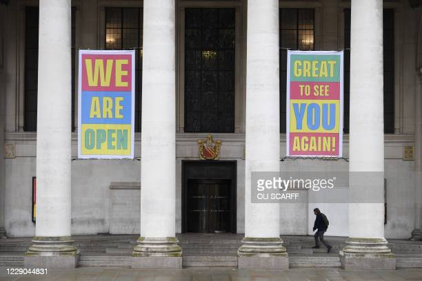 Man walks up the steps of the Manchester Central Library under banners declaring that it is open, in Manchester, north west England on October 13 as...