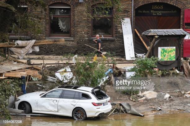 Man walks walks past a damaged car standing in the river Ahr amid debris and uprooted trees in the city of Altenahr, Rhineland-Palatinate, western...