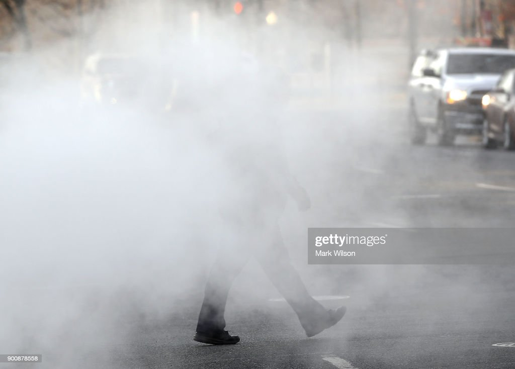 A man walks walks past a steam grate on January 3, 2018 in Washington, DC. A winter storm is traveling up the east coast overnight with significant accumulationsÊof snow possible.