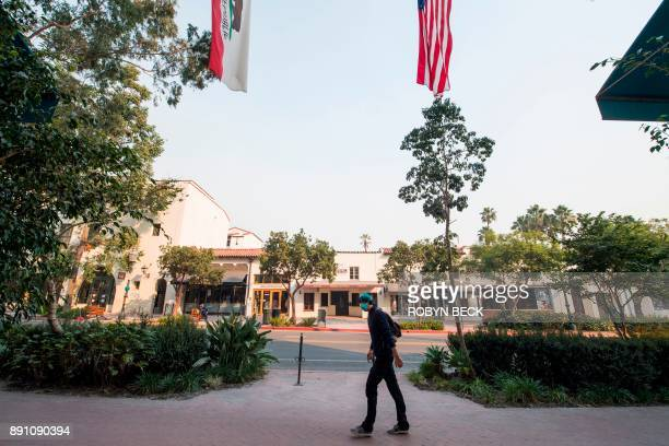 A man walks wearing a face mask to protect himself from smoke and ask from the Thomas Fire walks on State Street the main shopping street in Santa...