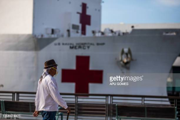 A man walks wearing facemak as a preventive measure against the spread of the COVID19 novel coronavirus in front of the US Navy Hospital ship Mercy...