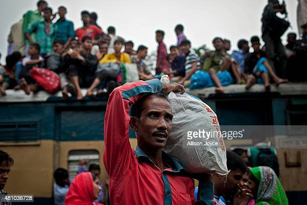 A man walks with a bag as Bangladeshi Muslims crowd onto a train to head home to their respective villages ahead of Eid AlFitr July 17 2015 in Dhaka...