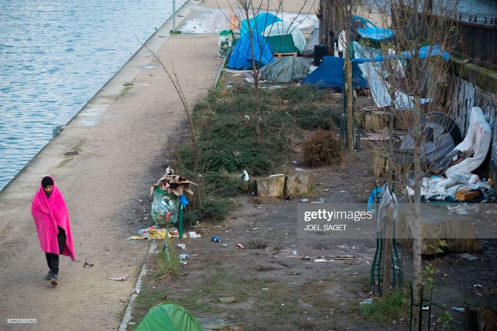 A man walks with a blanket over his shoulders near tents at a makeshift migrant camp, mainly made up of Afghans, along the Saint-Martin canal in Paris on February 21, 2018