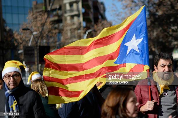 A man walks with a Catalan proindependence 'Estelada' flag after a demonstration to support Catalan political prisoners on December 24 2017 in front...