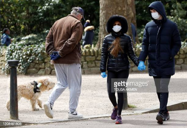 A man walks with a dog as a couple wearing gloves and face masks a a precautionary measure against Covid19 walk past to get their daily exercise...