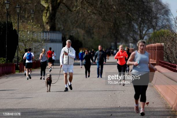 A man walks with a dog as people run past to get their daily exercise allowance in Battersea Park in London on March 28 as life in Britain continues...
