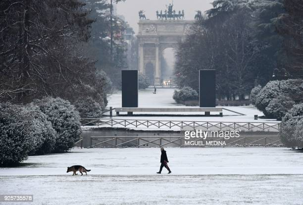 A man walks with a dog in Sempione garden after snowfall in Milan on March 1 2018 Fresh heavy snowfalls and icy blizzards were expected to lash...