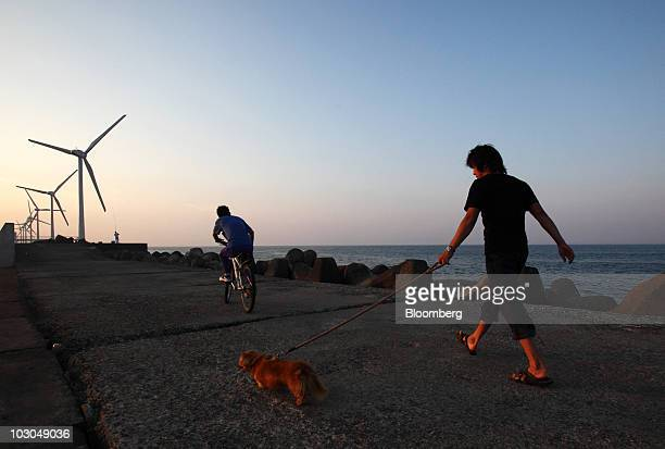 A man walks with a dog while a man cycles in front of wind turbines developed by Fuji Heavy Industries Ltd and Hitachi Ltd at the Wind Power Kamisu...