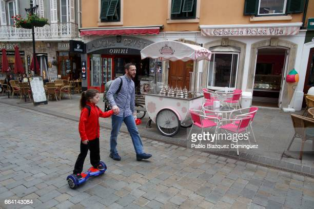 A man walks with a girl using a hoverboard in the street on April 3 2017 in Gibraltar Tensions have risen over Brexit negotiations for the Rock of...