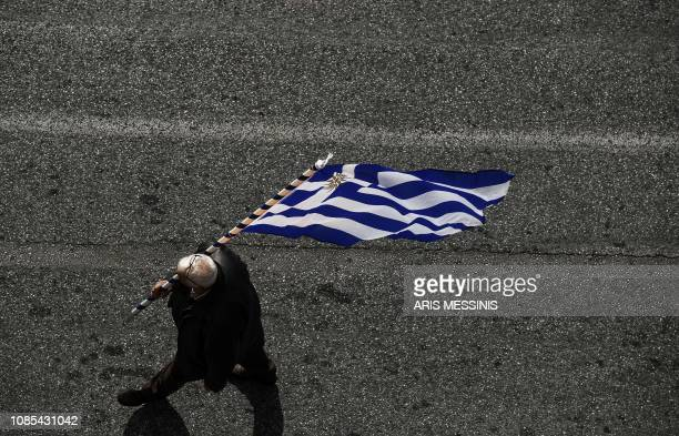A man walks with a Greek flag near the Greek Parliament during a demonstration against the agreement with Skopje to rename neighbouring country...