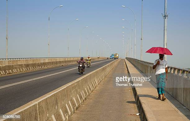 A man walks with a red parasol over a newly built concrete bridge on April 11 2016 in Khulna Bangladesh