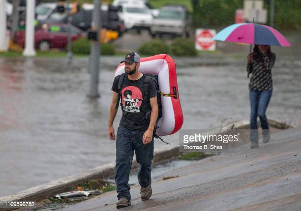 A man walks with a small float strapped to his back as he walks above the feeder back to his hotel off of highway 69 North on September 19 2019 in...