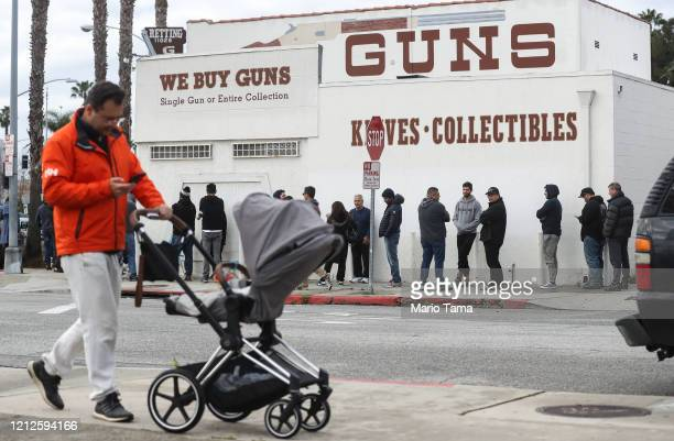 A man walks with a stroller as people stand in line outside the Martin B Retting Inc guns store on March 15 2020 in Culver City California The spread...