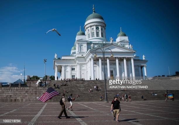 A man walks with a US flag at the Senate Square near the Presidential Palace where Russian and US Presidents meet for a summit in the Finnish capital...
