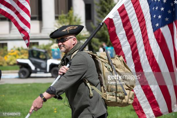 A man walks with an American flag as hundreds gather to protest the state's stayathome order at the Capitol building on April 19 2020 in Olympia...