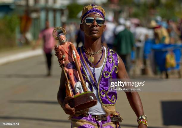 A man walks with an image of San Lazaro on December 16 2017 in La Habana Cuba Thousands of believers gather at the Shrine of San Lazaro on the...