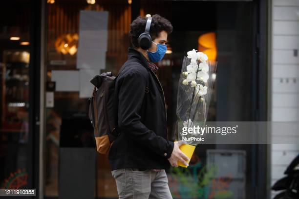 A man walks with an orchid in the street in Paris as a lockdown is imposed to slow the rate of the coronavirus disease in France May 5 2020 France...