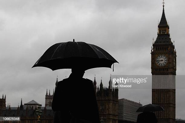 A man walks with an umbrella across Westminster Bridge on November 8 2010 in London England Forecasters have predicted storms across much of the...