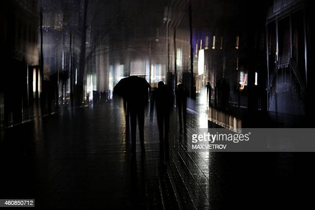 A man walks with an umbrella during a power outage in the Crimean city of Simferopol on December 26 2014 Crimea on December 24 and December 26...