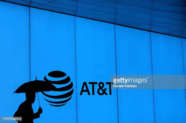 Man walks with an umbrella outside of AT&T corporate headquarters on March 13, 2020 in Dallas, Texas. AT&T is allowing employees to work remotely...