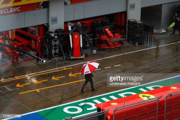 A man walks with an umbrella past the Ferrari's pit before the third practice session for the Formula One Styrian Grand Prix on July 11 2020 in...