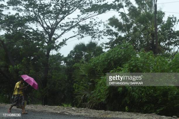A man walks with an umbrella under the rain ahead of the expected landfall of cyclone Amphan in Midnapore West Bengal on May 20 2020 India and...