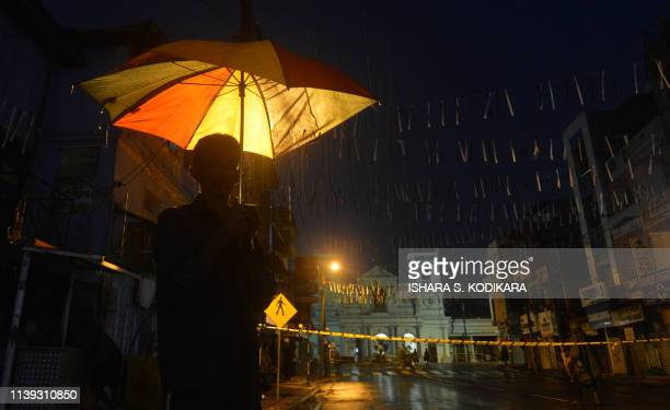 TOPSHOT A man walks with an umbrella under the rain near St Anthony's Shrine in Colombo on April 25 following a series of bomb blasts targeting...