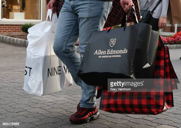 A man walks with bags from the Nine West Allen Edmonds and Woolrich stores at the Woodbury Common Premium Outlets Mall on October 21 2017 in Central...