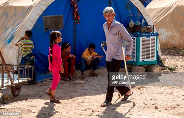 A man walks with crutches at a UNHCR refugee camp in Hammam alAlil on the outskirts of Mosul on July 12 2017 Iraqi Prime Minister Haidar AlAbadi...