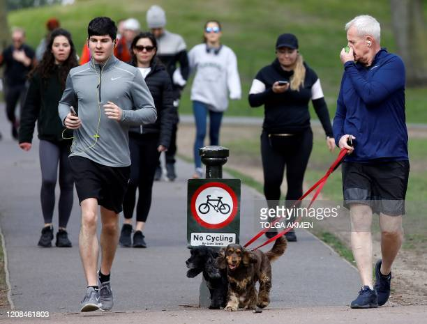 Man walks with dogs as people run past to get their daily exercise allowance in Battersea Park in London on March 28 as life in Britain continues...