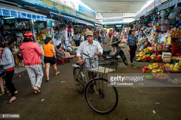 A man walks with his bicycle in the Con Market in the central Vietnamese city of Danang on November 11 as leaders from the 21member APEC organisation...