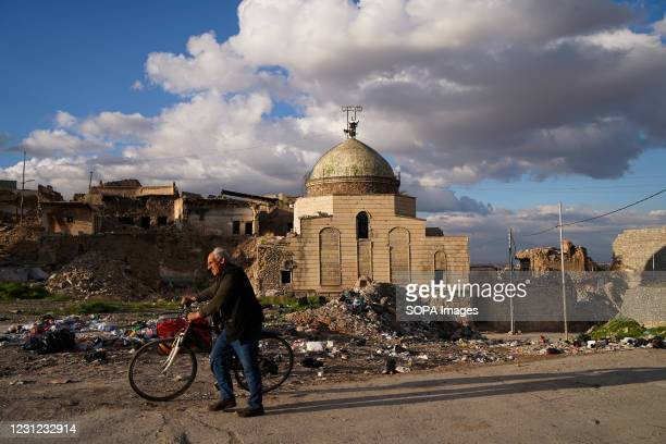 Man walks with his bicycle past the damaged mosque. The Umayyad Mosque which is located in the old area of the city of Mosul, was built in 638 AD and...