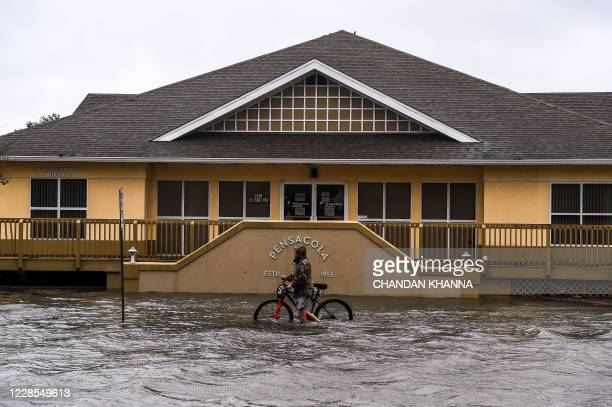 TOPSHOT A man walks with his bicycle through a street flooded by rains from Hurricane Sally in downtown Pensacola Florida on September 16 2020...