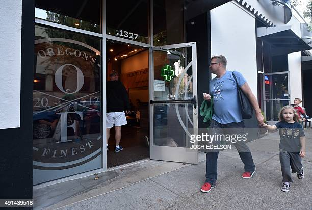 A man walks with his daughter near Oregon's Finest a marijuana dispensary in Portland Oregon on October 4 2015 As of October 1 2015 a limited amount...