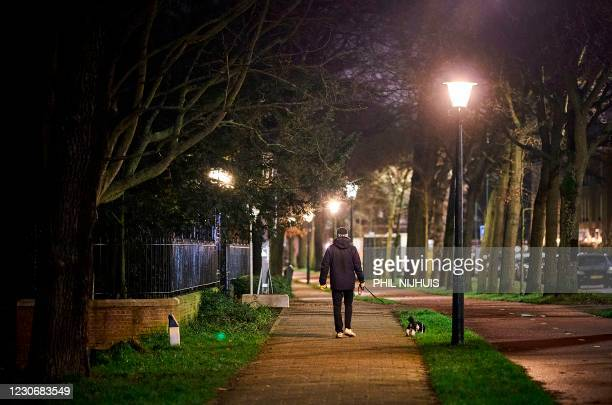 Man walks with his dog in The Hague, on January 19, 2021. - The outgoing cabinet is considering introducing a new curfew to curb the spread of the UK...