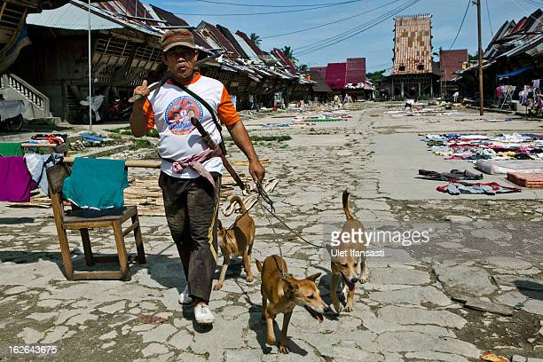 A man walks with his dogs as going to hunt in Bawomataluwo village on February 22 2013 in Nias Island Indonesia Some of historians and archaeologists...