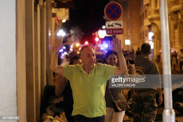 A man walks with his hands up as police officers carry out checks on people in the centre of French Riviera town of Nice after a truck that ploughed...