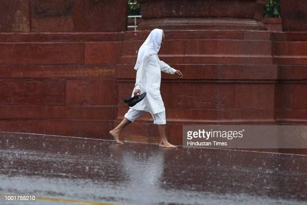 Man walks with his shoes in hand as it rains heavily near North Block on July 13, 2018 in New Delhi, India. The national capital witnessed heavy...