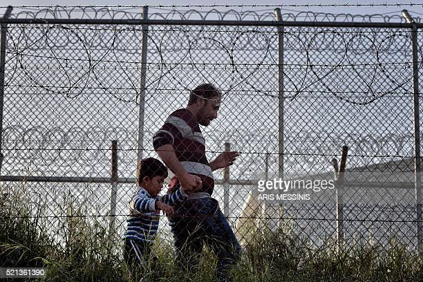 A man walks with his son in the Moria detention centre in Mytilene on April 15 on the eve of Pope Francis' visit Pope Francis was urged on April 14...