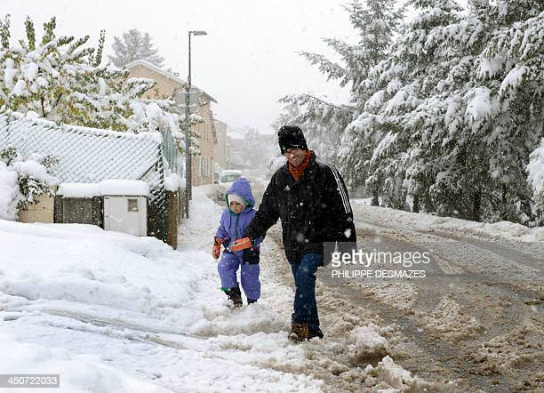 A man walks with his son in the snow on November 20 2013 in Cellieu village near SaintEtienne after heavy snowfall SaintEtienne awoke to around 30cm...