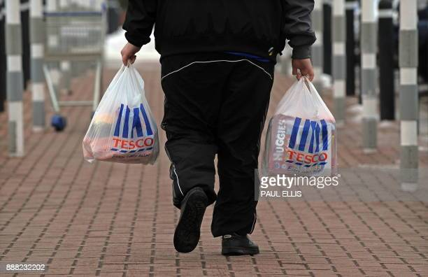 A man walks with shopping from a Tesco supermarket in Birkenhead northwest England on January 12 2010 Britain's biggest retailer supermarket group...