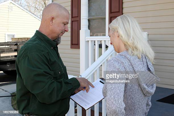 Man wanting woman to sign paper in front of house