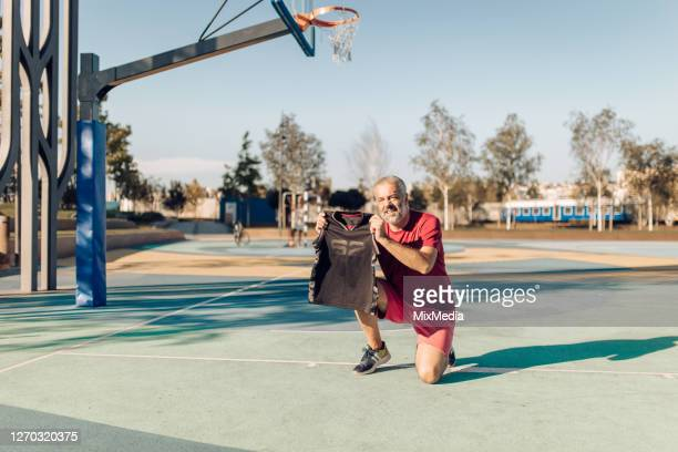 man wants to surprise his son with a new basketball jersey - new jersey stock pictures, royalty-free photos & images