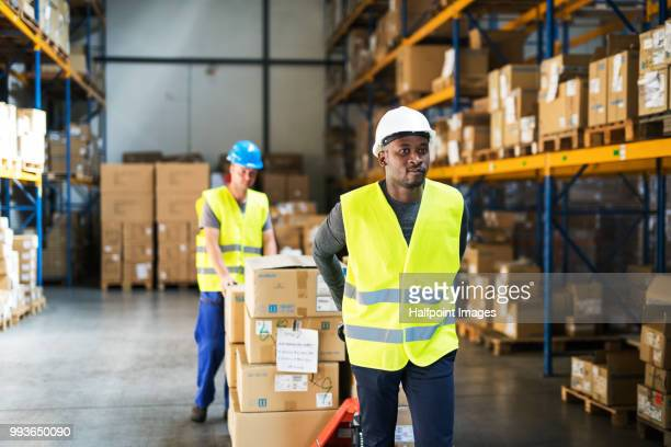 man warehouse workers pulling a pallet truck with boxes. - waistcoat stock pictures, royalty-free photos & images