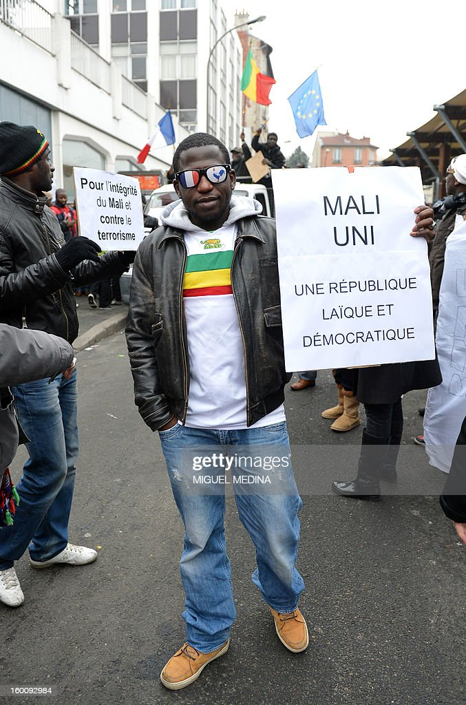 A man, waring glasses with painted French flag and French rooster symbol, holds a placard reading 'United Mali : a laic and democratic republic' during a demonstration, organized by Malian associations, in support of the liberation forces of Mali on January 26, 2013 in Montreuil, near Paris. Placard reads 'For a united Mali, against terrorism'.