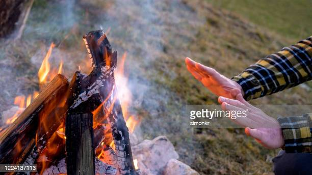 man warming hands over campfire - warming up stock pictures, royalty-free photos & images