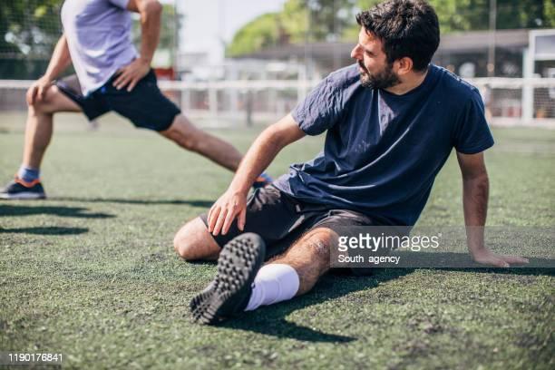 mann wärmt sich für fußballspiel auf - aufwärmen stock-fotos und bilder
