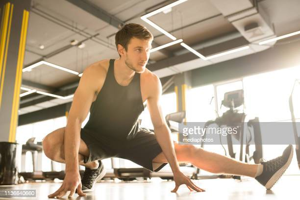 man warming up in gym - one man only stock pictures, royalty-free photos & images